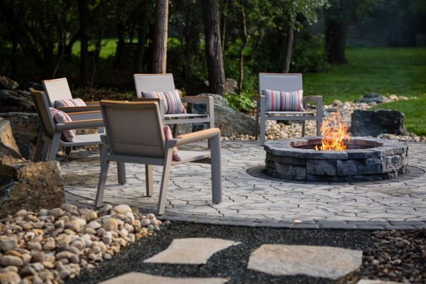 A circular patio with outdoor chairs and a fire pit in the middle.