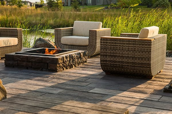 Fire pit on a patio with patio chairs surrounding it, a creek is situation behind the scene.
